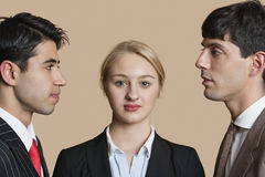 Portrait of a young businesswoman with male colleagues staring at each other over colored background Stock Image
