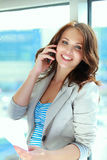 Portrait of young businesswoman with mobile phone on office hallway Royalty Free Stock Images