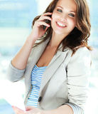 Portrait of young businesswoman with mobile phone on office hallway.  Royalty Free Stock Image