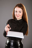 Portrait of a young businesswoman. With pen and documents looking up Stock Photography