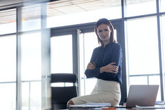 Portrait of young businesswoman sitting arms crossed on desk in office Stock Photography