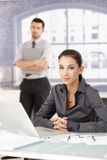 Portrait of young businesswoman sitting at desk Stock Images