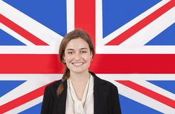 Portrait of young businesswoman smiling over British flag Royalty Free Stock Photo