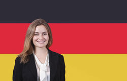 Portrait of young businesswoman smiling over German flag Stock Photos