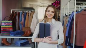 Portrait of young businesswoman standing in her clothing boutique, holding tablet, smiling and looking at camera. Spacious store with women`s clothes in stock footage