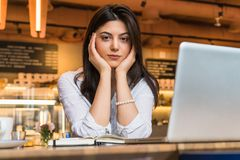 Portrait of young businesswoman, student, dressed in white blouse, sitting at table in cafe in front of computer. Stock Photos