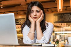 Portrait of young businesswoman, student, dressed in white blouse, sitting at table in cafe in front of computer. Royalty Free Stock Photography