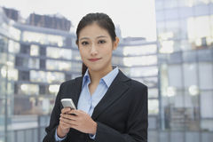 Portrait of young businesswoman texting on her phone, cityscape in background Royalty Free Stock Images