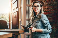 Portrait of young businesswoman in trendy glasses,sitting in cafe in front of laptop, holding tablet computer, working. stock photos