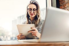 Portrait of young businesswoman in trendy glasses,sitting in cafe in front of laptop, using tablet computer, working. stock images