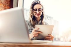 Portrait of young businesswoman in trendy glasses,sitting in cafe in front of laptop, using tablet computer, working. stock photography