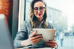 Portrait of young businesswoman in trendy glasses,sitting in cafe in front of laptop, using tablet computer, working. stock photos
