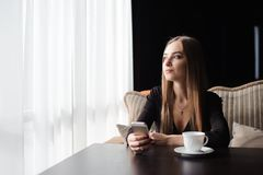 Portrait of young businesswoman use mobile phone while sitting i royalty free stock images