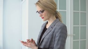 Portrait young businesswoman using smartphone holding mobile gadget, girl smile and texting message. Portrait young businesswoman using smartphone holding stock video footage