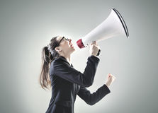 Portrait of a young businesswoman yelling over the megaphone Royalty Free Stock Images