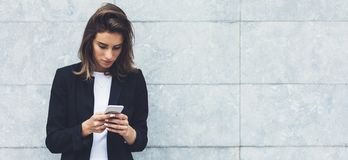Portrait young businesswomen in black suit using smartphone on background concrete gray wall mockup, hipster manager stock photography