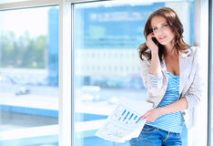 Portrait of young busineswoman standing in office lobby.  Royalty Free Stock Images