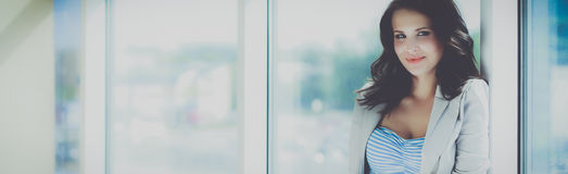 Portrait of young busineswoman standing in office lobby.  Royalty Free Stock Image