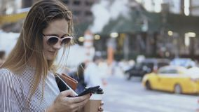 Portrait of young busy businesswoman holding the coffee cup and documents and using the smartphone on the street. Beautiful female working in Internet from stock video footage