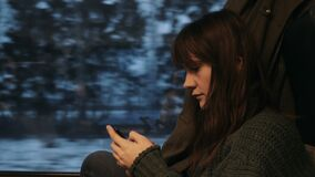 Portrait of young calm thoughtful beautiful Caucasian passenger woman using smartphone on train window seat slow motion. stock video