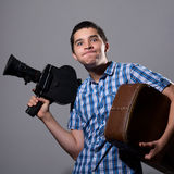 Portrait of a young cameraman with old movie camera and a suitca Royalty Free Stock Images
