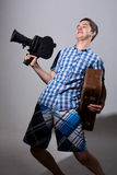 Portrait of a young cameraman with old movie camera and a suitca Royalty Free Stock Photography