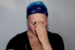 Portrait of a young cancer patient in a headscarf looks distressed as she is holding hand to her face. Young cancer patient in a headscarf Stock Photos