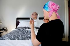 Portrait of a young cancer patient in a headscarf looks shocked at her reflection in the mirror Royalty Free Stock Photos