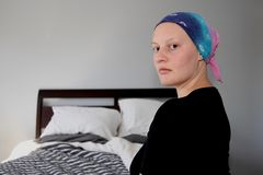 Portrait of a young cancer patient turning to looking at camera. Young cancer patient in a headscarf Royalty Free Stock Photos