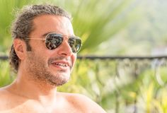 Portrait of a young candid Caucasian man wearing sunglasses under the sunlight with blurry background. Portrait of a young candid Caucasian man wearing Stock Photos