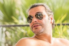 Portrait of a young candid Caucasian man wearing sunglasses under the sunlight with blurry background. Portrait of a young candid Caucasian man wearing Stock Photo