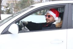 Portrait of young car driver with santa hat enjoying the snow an. D sunny dan. Holiday and winter concept royalty free stock photo