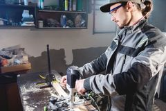 Portrait of a young carpenter joiner with electric milling cutter in the hands of a worker in a home workshop. Starting royalty free stock photo
