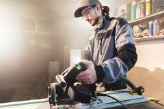 Portrait of a young carpenter joiner with manual circular power saw in the hands of a worker in a home workshop stock photos