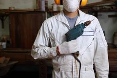 Portrait of young carpenter with safety uniform holding electric drill in carpentry workshop. Portrait of young carpenter with safety uniform holding electric Stock Photography