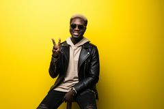 Portrait of a young casual afro american man posing in sunglasses and gesturing victory sign over yellow background royalty free stock photography