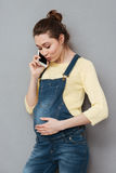 Portrait of a young casual pregnant woman with mobile phone. On a gray background Royalty Free Stock Photography