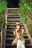 Portrait of a young casual woman in hat sitting on a vintage wooden stairs outdoor. Stock Photo