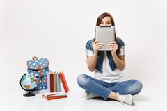 Portrait of young casual woman student covering face with tablet pc computer sitting near globe backpack school books. Isolated on white background. Education stock image