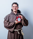 Portrait of Young catholic monk with alarm clock Royalty Free Stock Photography