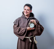 Portrait of Young catholic monk with alarm clock Royalty Free Stock Images