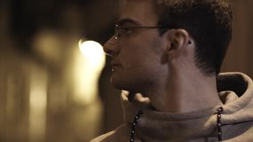 Portrait of young man in glasses out of breath turns around in alleyway. Portrait of young cauasian unshaved man in glasses and gray hoodie out of breath turns stock video footage