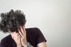 Portrait of a young, Caucasian, brunet, curly haired man covering his face with hands on white background. stock photo