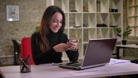 Portrait of young caucasian brunette businesswoman surfing feed on smartphone and smiling happily in office. Portrait of young caucasian brunette businesswoman stock footage