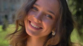 Portrait of a young smiling caucasian brunette in the park, university in the background stock video footage