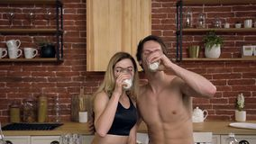 Portrait of a young Caucasian couple drinks healthy milk in the kitchen at home. Healthy drink, diet, healthy lifestyle stock video footage