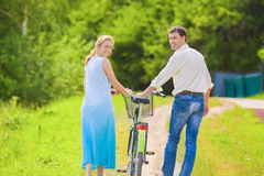 Portrait of Young Caucasian Couple Leading One Bicycle Together Stock Photo
