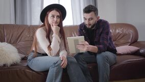 Portrait of young Caucasian couple sitting on couch with tablet and talking. Irritated girl in elegant hat signing and stock video footage