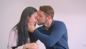 Portrait of young caucasian couple sitting on floor of new empty flat hugging and kissing tenderly on white wall. Background stock video