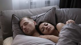 Portrait of young caucasian couple sleeping in the bed at home on the grey bed sheets. Morning time stock video footage
